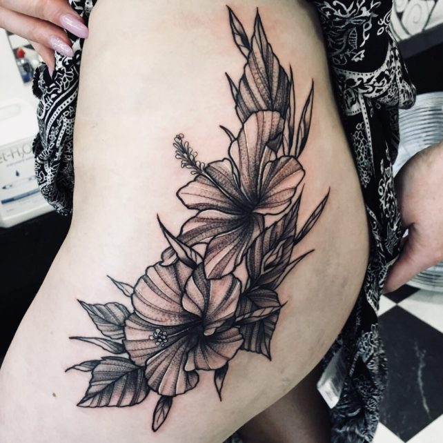 Hibiscus tattoo on females hip done at Sharp Art Studios