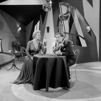 "Shatner and McNeil sitting at a table on the set of ""Forever Galatea."""