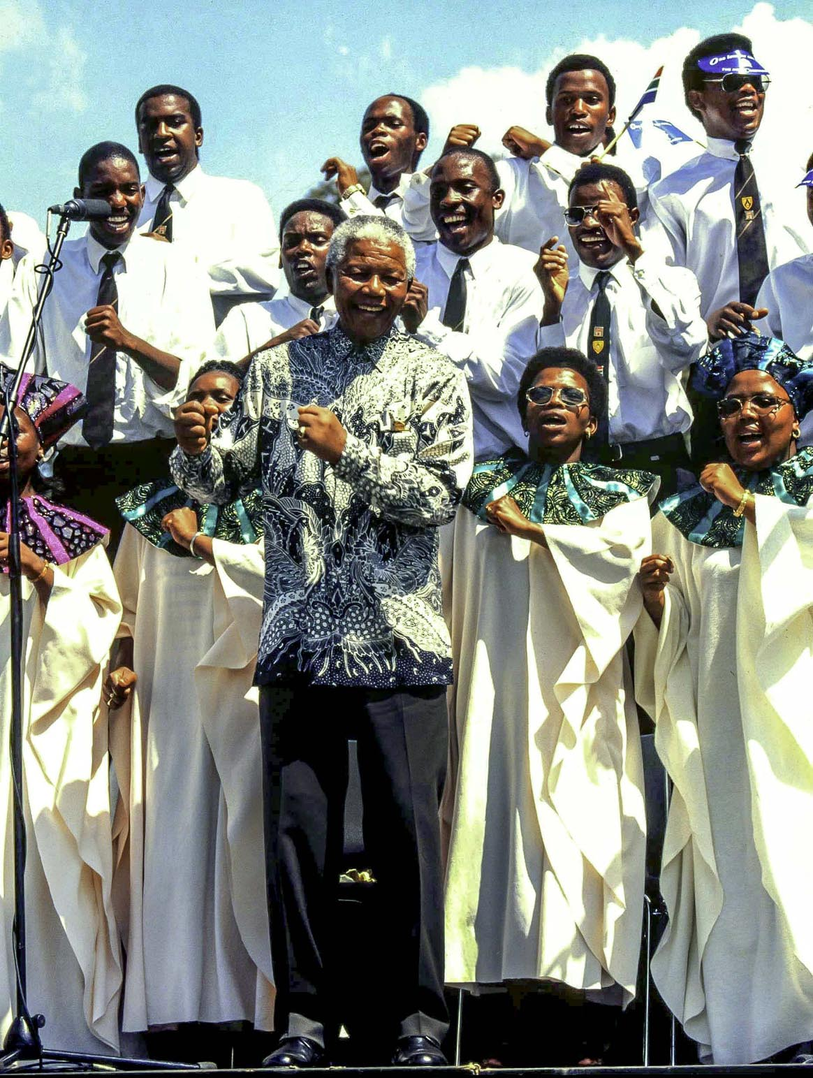 971115SH20:SAFRICA:PERSONALITY:POLITICS:GOVERNMENT:1997 - President Mandela and the choir at the singing of the constitution ceremony, doing the 'Madiba Jive' (Photo: Shuan Harris / www.afrikamoves.co.za)