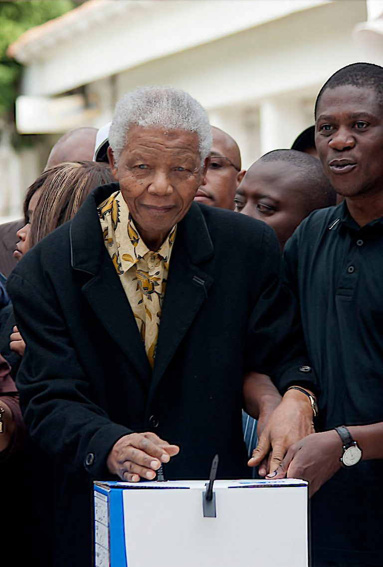 20090422SH044 Nelson Rolihlahla Mandela votes for the last time in the 2009 National Elections, he is being steadied by the Arts and Culture Minister at the time Mr.Paul Mashatile. (Photo © Shaun Harris / www.afrikamoves.co.za)