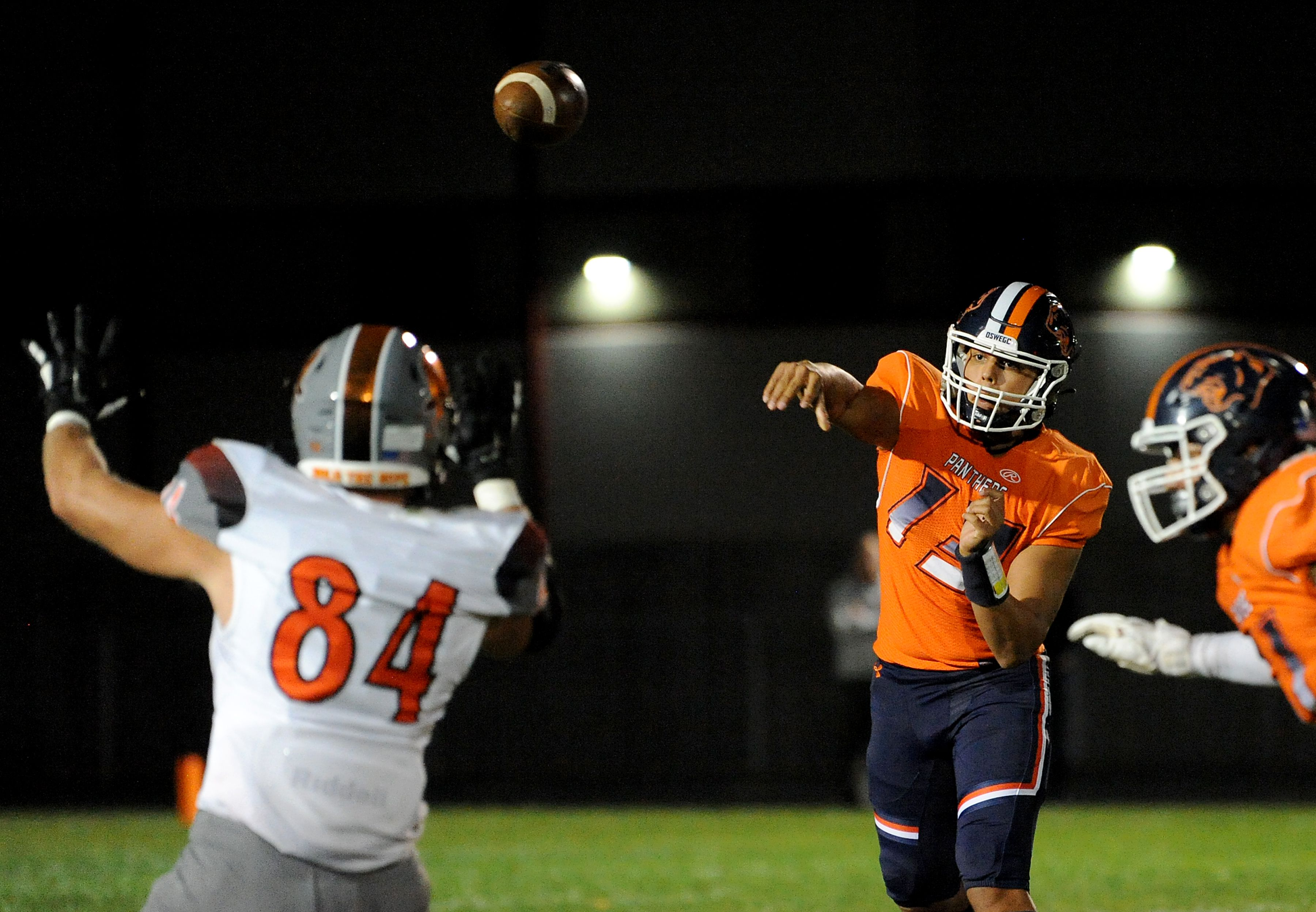 Oswego quarterback Cruz Jr Ibarra (13) tosses pass in the direction of Minooka defensive lineman Will DeBold (84) during a varsity football game at Oswego High School on Friday.