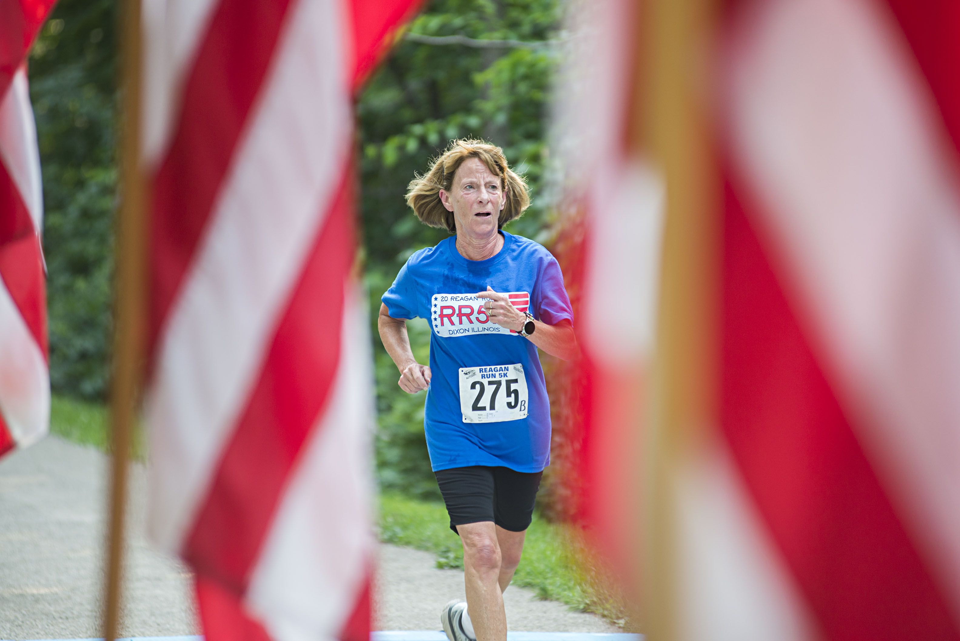 Flags flank the finish line as Jill Stoker of Dixon completes her race.
