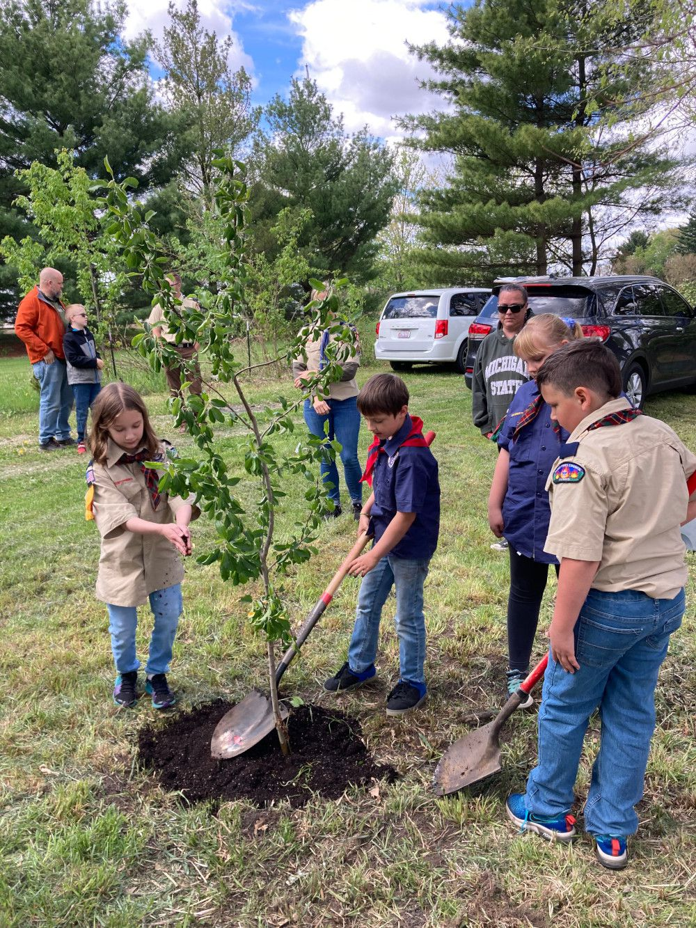 Scouts and leaders of Somonauk Cub Pack 335 planting apple trees.
