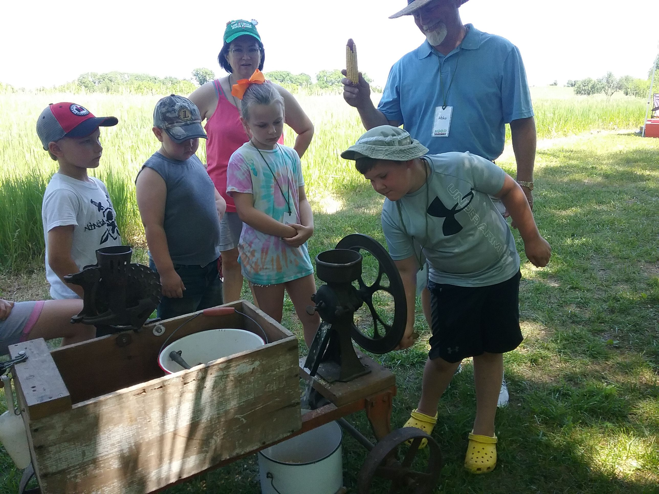 Grinding corn pioneer activity at Christian Day Camp held at Wells Barren Grove, Neponset.