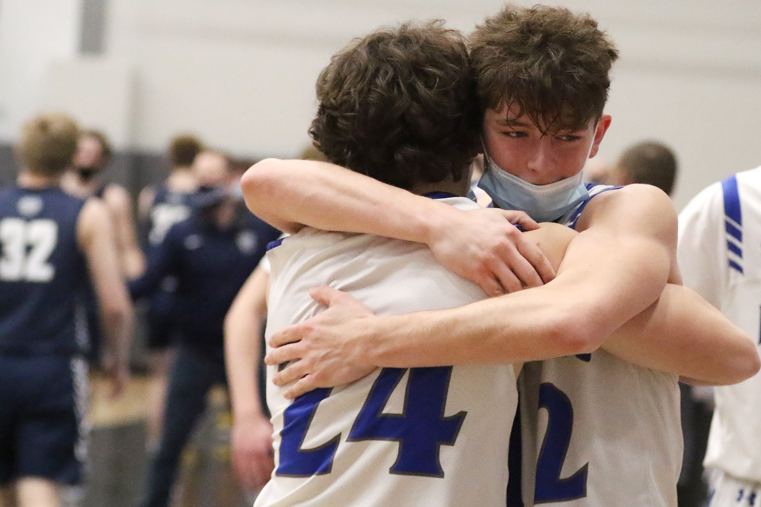 Burlington Central's Steven Langtim, facing, hugs teammate Matthew Lemon after coming out of the game late in the fourth quarter Saturday.