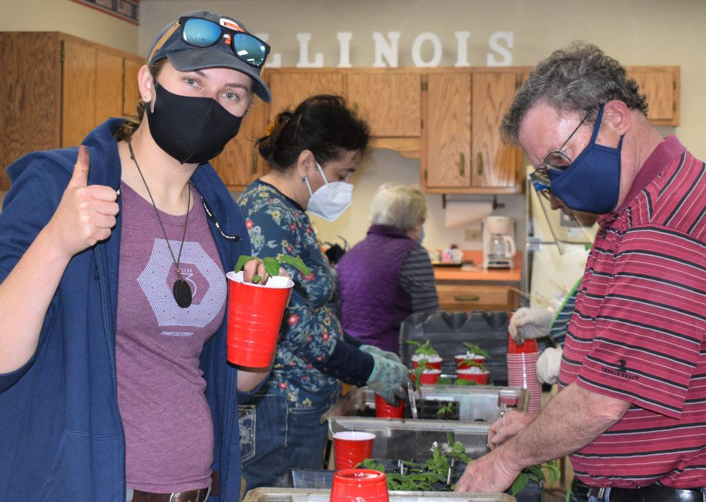 Kendall County Master Gardener volunteers prepare vegetable transplants for the plant sale. They grew 14 varieties of tomatoes and 8 kinds of peppers with a total of about 600 vegetable plants.