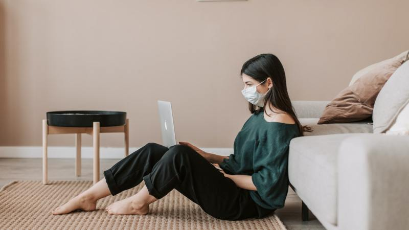 girl reading on laptop with mask