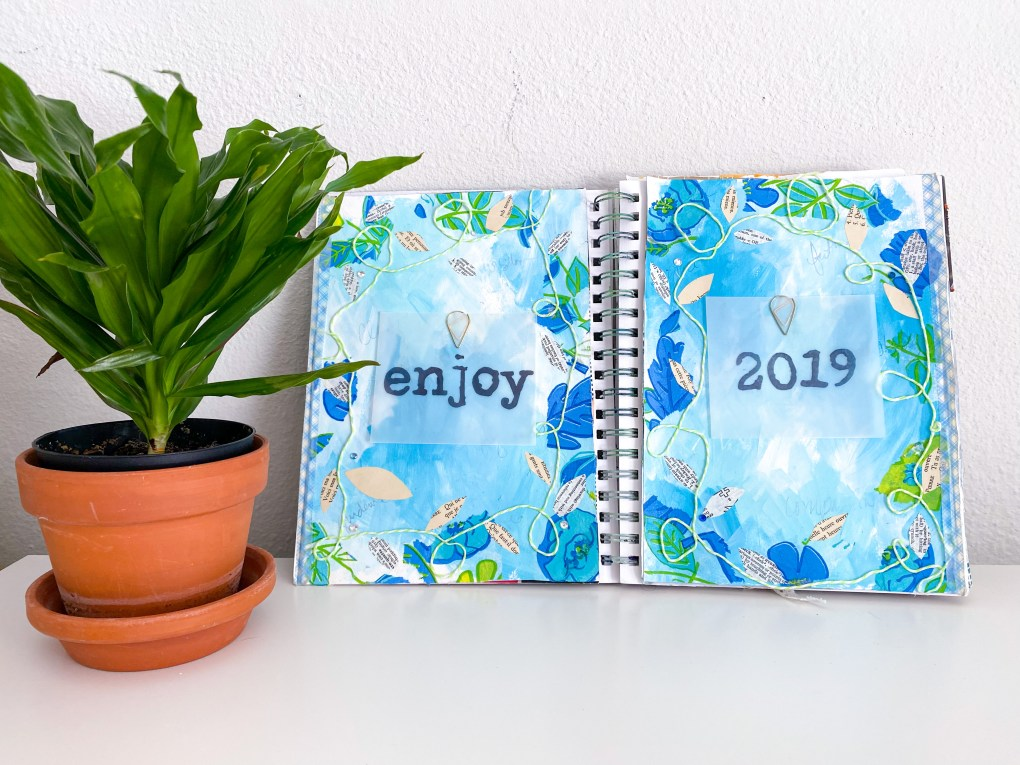 Spiral bound notebook with word of the year enjoy vision board.