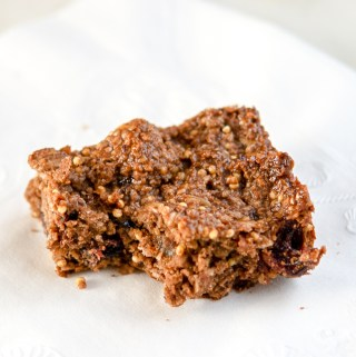 Photo of oat-y cocoa granola bar on a white napkin, with a bite out of it.