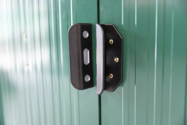 A picture of a closed door of a metal shed. It's a close up of the black plastic handles and the shed behind them is a rich green colour.