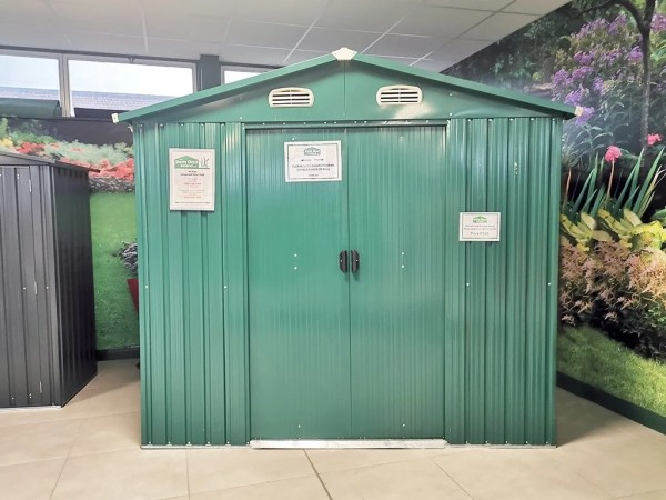 A front on view of a green, steel shed against a floral wallpaper, in the Sheds Direct Ireland showroom.