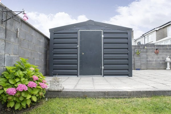 A heavy Duty, PVC Coated Shed in a Dublin garden. There is grass in the foregroiund and a pink flower to the left. The shed is sitting on