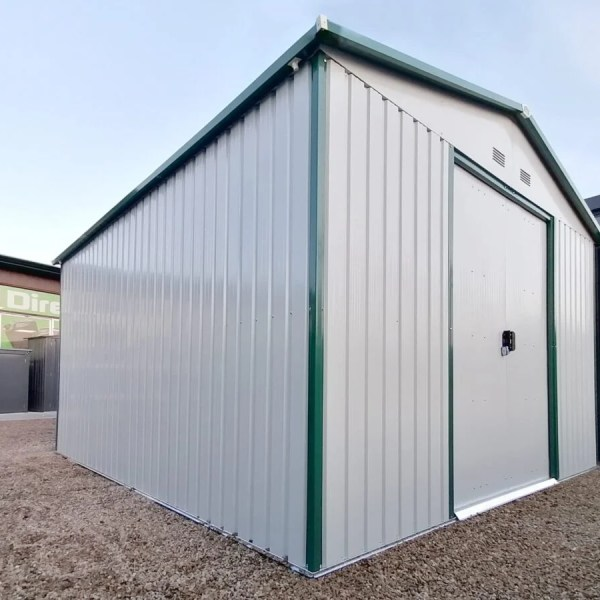 The Colossus Shed on the sheds direct ireland showroom as seen from a low angle. The doors and panels are white, the trim is green and above is a clear blue sky.