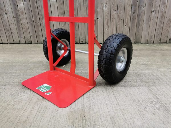 The base plate of the red p-handle sack truck. It has a Sheds Direct Ireland sticker on it. The plate is solid and fixed, it doesn't move or bend in any way. The wheels are very thick and have deep grooves in them. They are black with silver inserts.