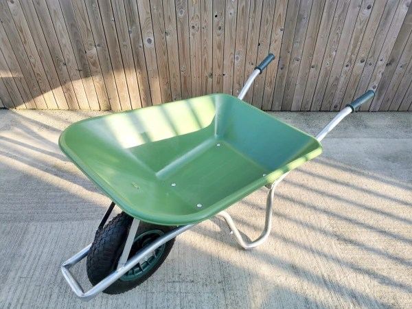 The wheelbarrow as seen from above. It is green with steel handles, a square wheel protector and black handles and tyre