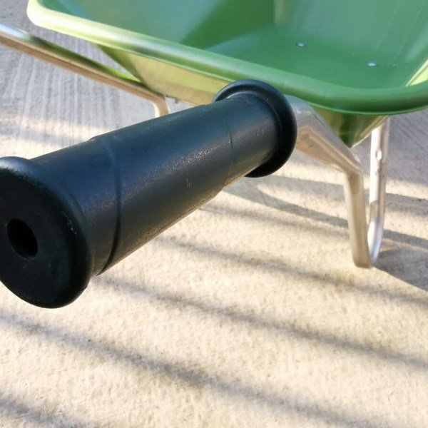 A detail of the handle on this wheelbarrow. It's a black rubber grip with bevels at either end.