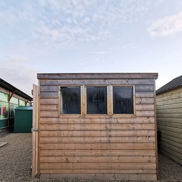 The side of the cabin shed in the showroom. It is a wide angled shot and the sky has some small clouds in the distance. The clouds are orange due to the sunrise. The shed has three black windows which have some morning dew on them. The wood is a pale colour and the wooden slats are horizontal