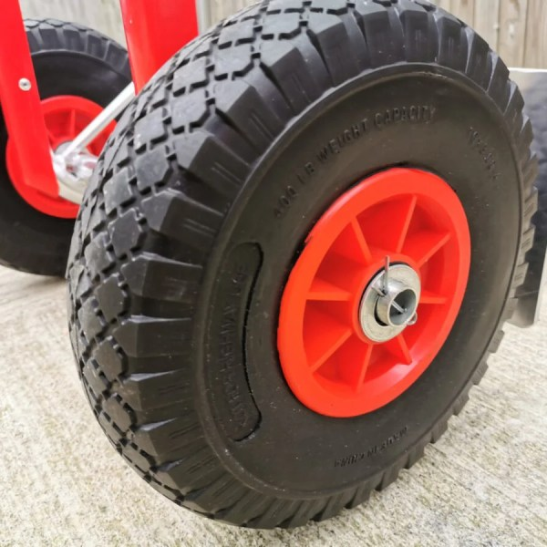 Detail image of the wheel on the aluminium sack truck. The wheels are balck with thick inlaid grooves for support. The internal wheel structure is bright red with a silver cap