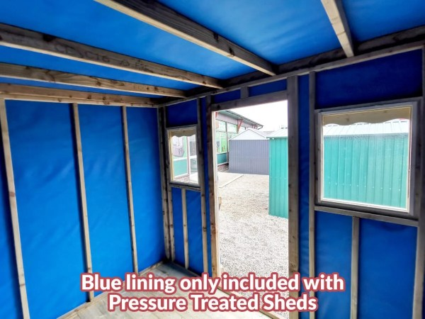 The inside of a wooden cabin. It is lined with blue felt and there are wooden joysts there for support.