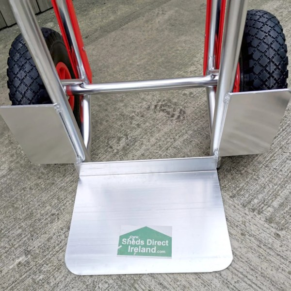 The metal base plate of the aluminium sack truck. It has two wheel protectors either side and there is a Sheds Direct Ireland sticker on it too.