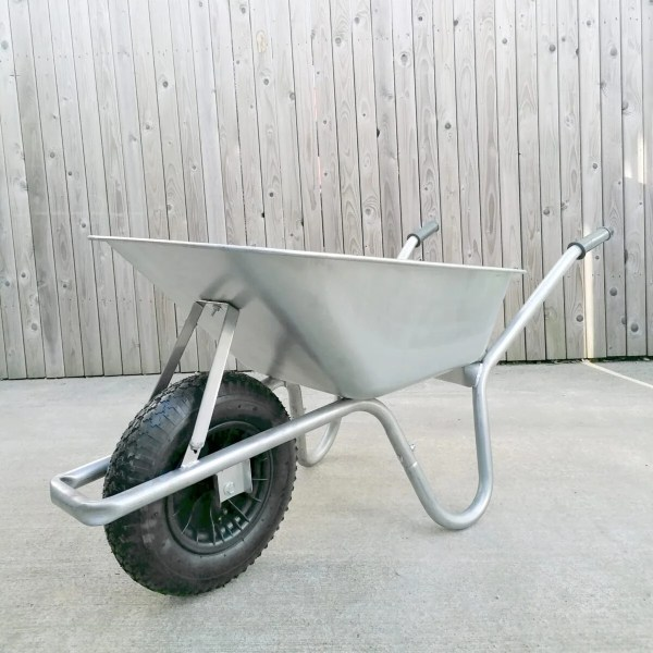 A steel wheelbarrow standing upright against a wooden fence