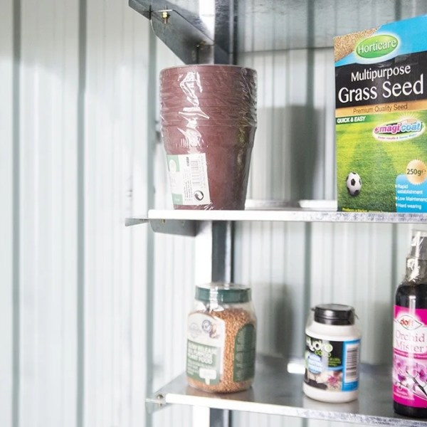 Metal Took Shelves mounted on the inside of a steel shed. There is a blue and green box of bird seed, a pack of plastic plant pots, an orange box of grass seed, a small white jar of 'loco coco' and a purple, wine-bottle shaped bottle of 'Orchid Mister' on the shelves. The ehslves themselves are a patchy steel.