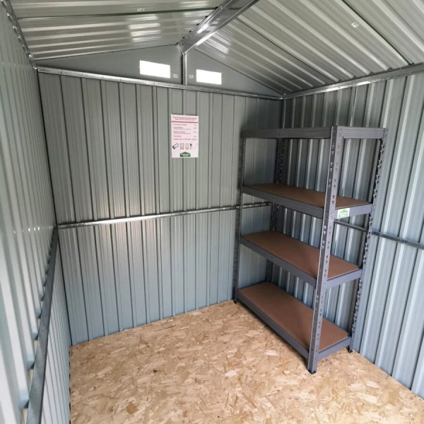 An inside view of the 6ft x 8ft Steel Shed. The walls are grey and the sheets are vertically laid. The roof has a shiny metal frame and there are two vents at the back wall also. The floor is a pale plywood and sitting on top of it in one corner is a large shelving unit.