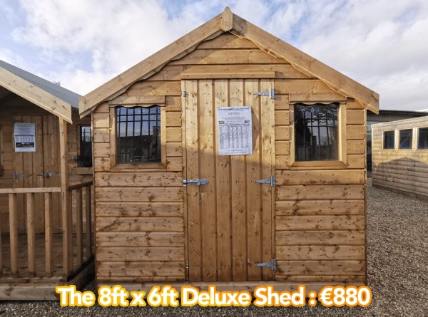 8x8 Deluxe Shed Shed as seen from outside, face-on. There are two windows, a peaked apex and the door is closed. The wood is a darker, more golden colour than inside.