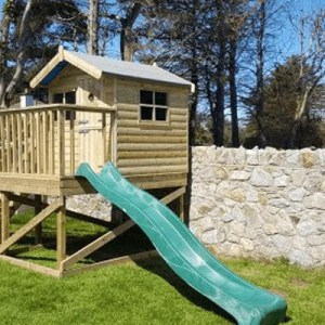 A wooden, raised treehouse with a green slide attached. The picture was taken on a sunny day and the shadows from the roof are harsh on the wood.
