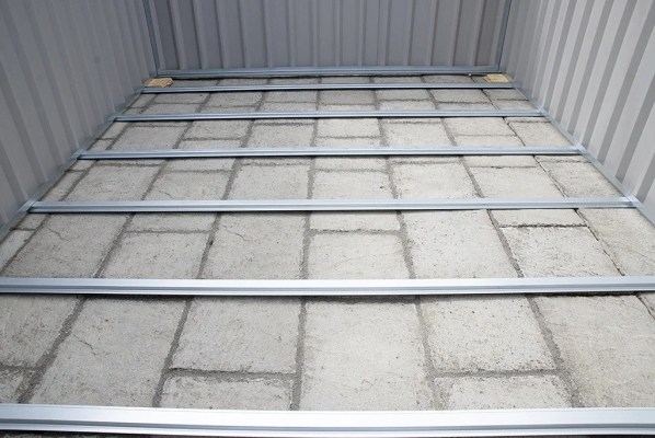 The floor frame of a PVC Cladded shed. You can see the metal bars of the frame, and the paving slabs underneath it. There is no 'floor' to speak of. Wooden plywood would suit on top of this.