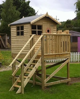 A Children's wooden treehouse. It is elevated on stilts, with a ladder leading up to the top floor. There are two windows visible and a small 'peep hole' on the front door