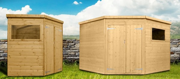 Two corner sheds set up beside each other. One is in a profile view, the other is face on. The wood is a golden, pale colour. Each shed has one window. They are set against an old irish stone wall, witha . bright blue sky behind the,