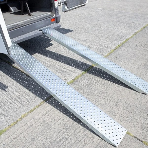Car Ramps made of Galvanised Steel attached to the back of a Bus. The bus has the doors open and the steel ramps are reflecting the sun into the camera. The ramps support 1500kg.