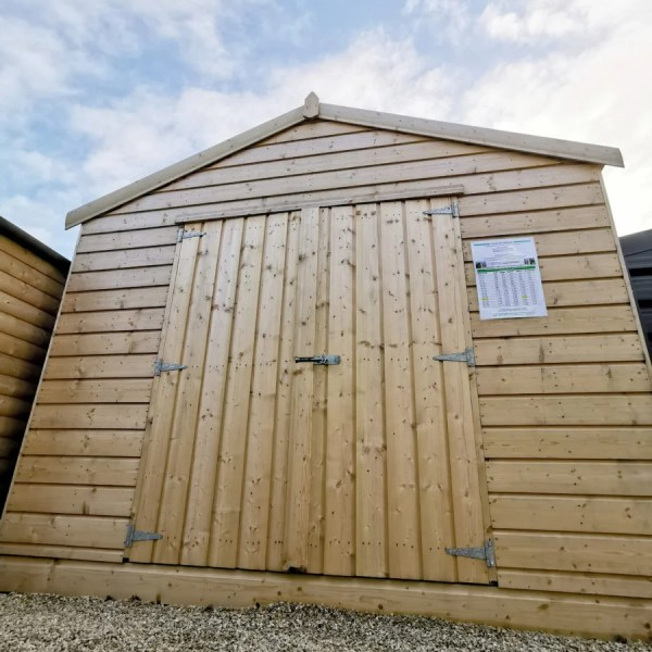 a Taller Wooden Shed as seen from a low angle. It's golden-brown, with horizontal wooden planks on the body and vertical planks on the door. There is a bolt lock and 3 hinges on each door. The sky is bright blue with dotted, but sweeping clouds above.
