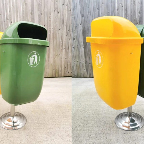 Plastic Bins for Schools against a wooden wall. There are 2 bins - one green and one yellow. They are connected to a silver, bevelled base. They both have images of a cartoon man dropping his litter in the bin on them.