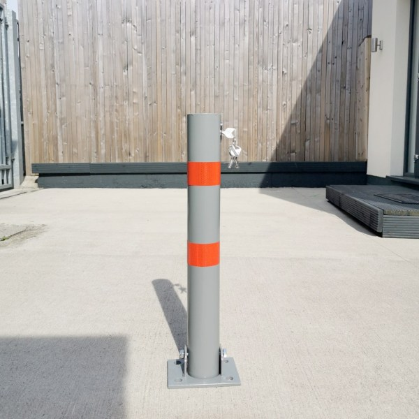 The Parking Pole from Sheds Direct Ireland. It's a tall, grey pole with red reflective stripes on it. It's sitting on a concrete pavement, but it's not bolted into position. It's there for display purposes only.