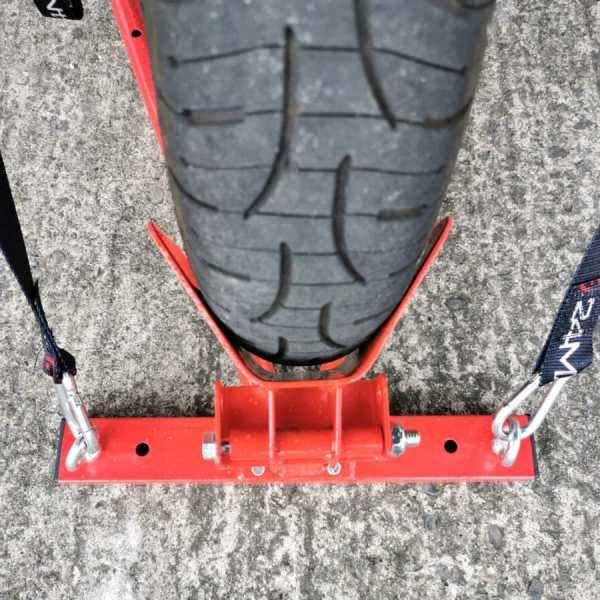 A top down view of the stand, showing the wheel in the back port. There are black and red cable straps holding the wheel securely in position. There are deep traction grooves on the wheel.