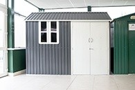 A grey and cream Steel Cottage Shed in the Sheds Direct Ireland showroom. The floor is a cream tile. The shed has grey sheet walls, a cream door and a grey roof. There is a window which is dissected into 4 panels on the left. The door is a double oor and it is on the right.