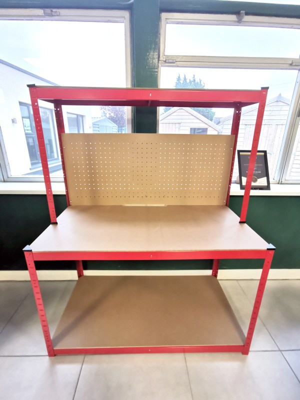 A front view of the work bench. It's bright red and it's sitting against a wall in the Sheds Direct Ireland showroom. The peg board is visible, but it's clear that it doesn't connect from the top to middle shelf.