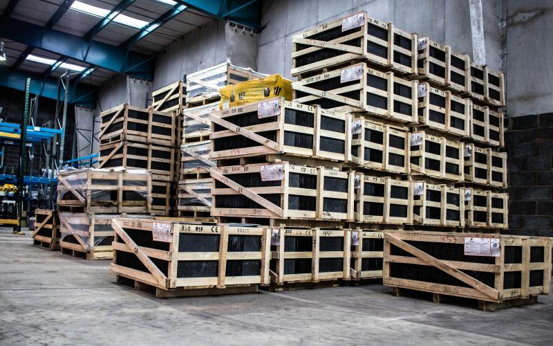 An inside view of a large warehouse. There are hundreds of pale brown pallets stacked high with thickly wrapped, black boxes. There light above is fluorescent and it casts long shadows on the stuff below.