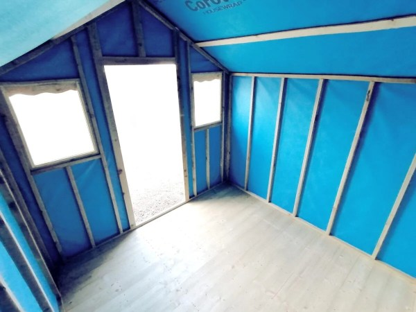 The blue interior of the overhang shed. The outside is bright and light spills into this shed from a low angle