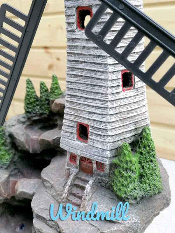 A close up, macro detail of the base of the windmill water feature. The steps up to the door and the small painted details are cute and clean.
