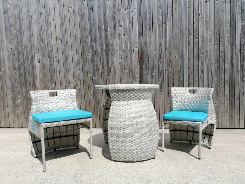 The balcony table and chairs set from Sheds Direct Ireland against a wooden wall. The chairs have the apperance of wicker and there is a bright baby blue cushion on each one. The table has a barrel-like appearance with a flat top. On the top of the unit sits a shiny, black glass tabletop.