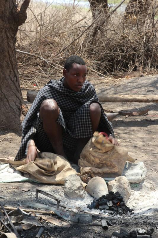 Junger Datogamann entfacht das Feuer mithilfe von Lederbälgen