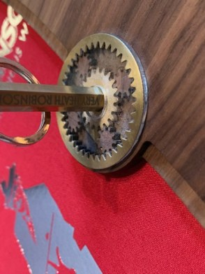 Colour photo of Super De Luxe Presentation Box open with close-up of brass hexagonal key in brass cog wheels of lock.