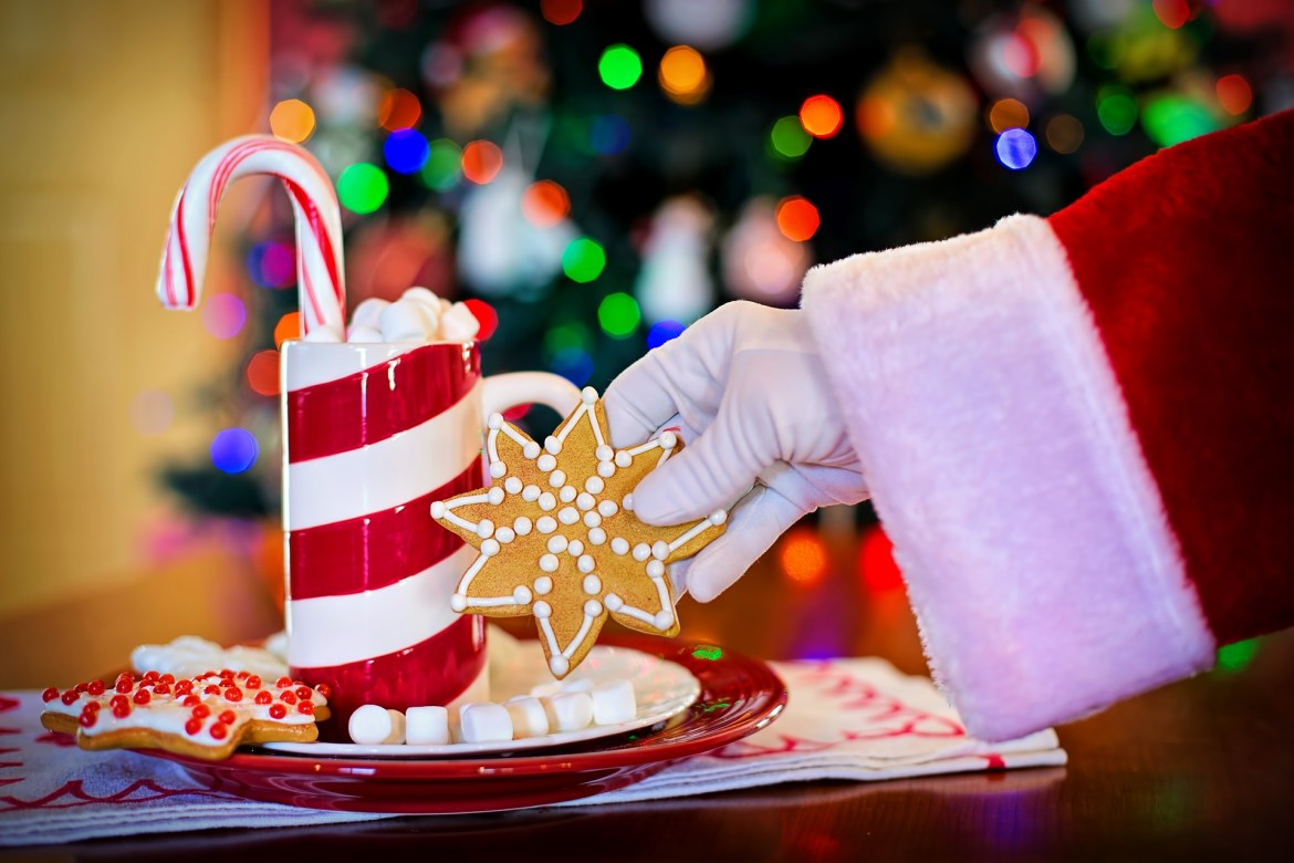 Santa's hand picking up a cookie from plate that's next to a mug of hot chocolate with a candy cane sticking out of the top