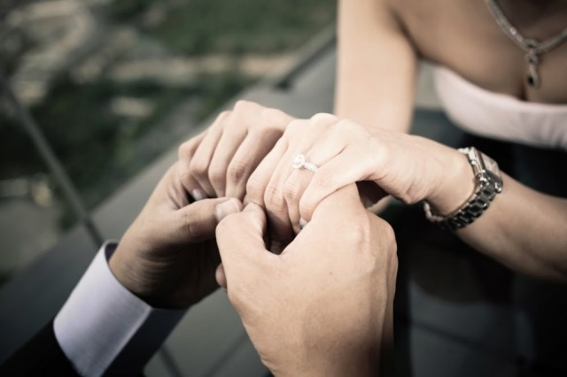 couple holding hands, showing the engagement ring