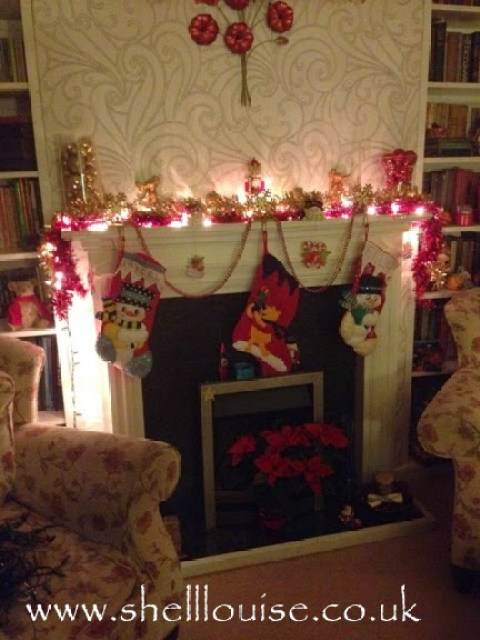 Fireplace decorated and lit with fairy lights