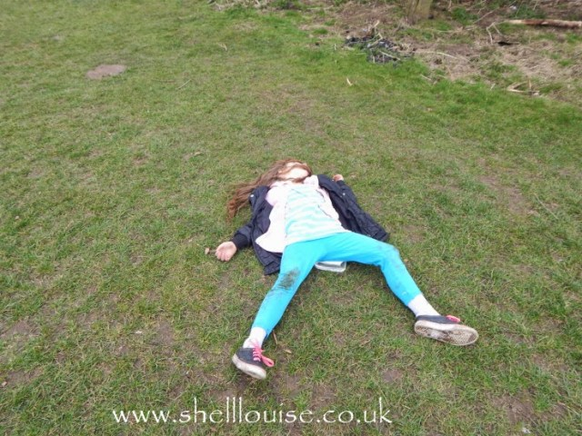 Ella lying on the wet grass at Rufford Abbey