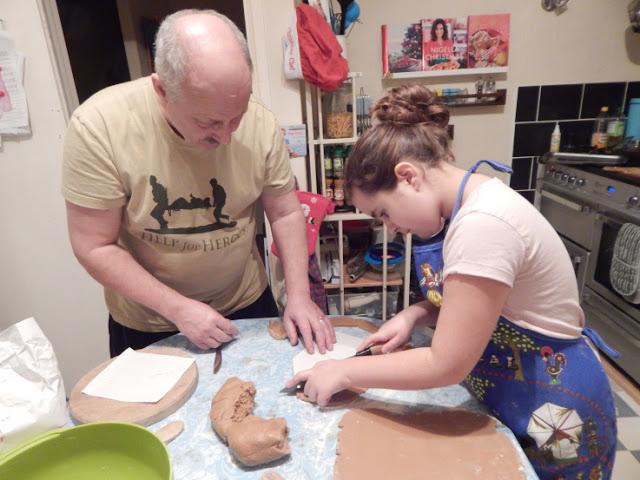 Daddy helping Kaycee cut the dough